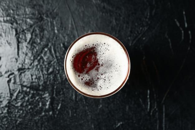 Vaso de cerveza en la mesa negra, vista superior