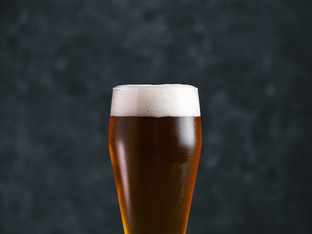 Vaso de cerveza en una mesa oscura de cerca