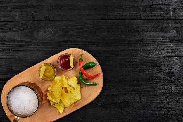 Vaso de cerveza con nachos chips sobre un fondo de madera