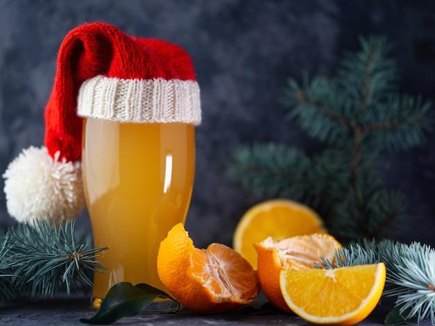 Un vaso de cerveza de navidad en un gorro de papá noel en una mesa oscura