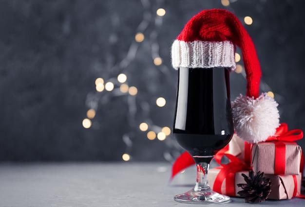 Vaso de cerveza negra artesanal stout, portero con sombrero de santa en mesa de vacaciones copyspace