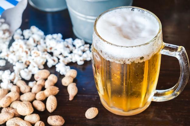 Vaso de cerveza nueces y palomitas de maíz
