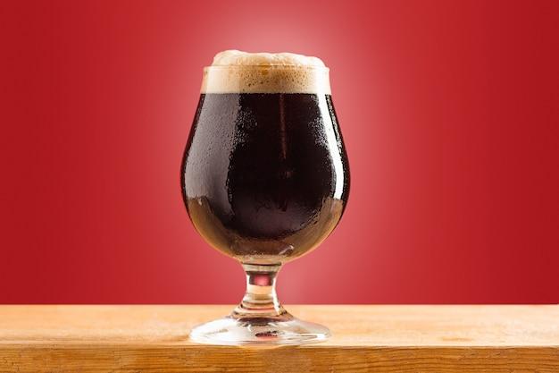 Vaso de cerveza oscura espumosa fría sobre una vieja mesa de madera