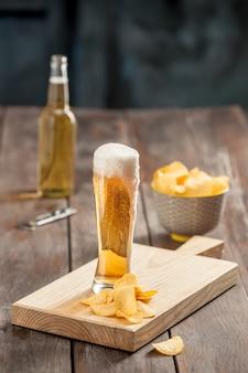 El vaso de cerveza y papas fritas, pistachos aislado en un blanco