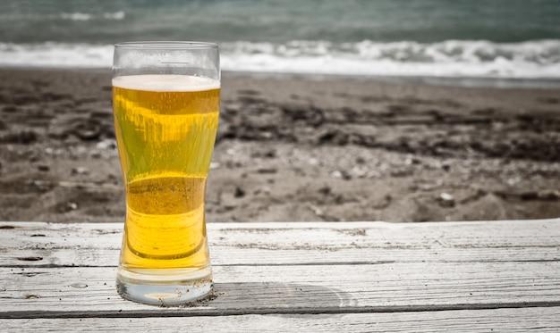Vaso de cerveza pilsner dorada clara sobre una mesa rústica al aire libre en la arena junto al mar con arena oscura y rompiendo olas en el fondo