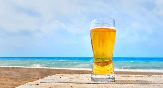 Vaso de cerveza pilsner dorada pálida en la playa de pie sobre una mesa de madera rústica con vistas a una playa de arena tropical y el tranquilo océano azul conceptual de las vacaciones de verano