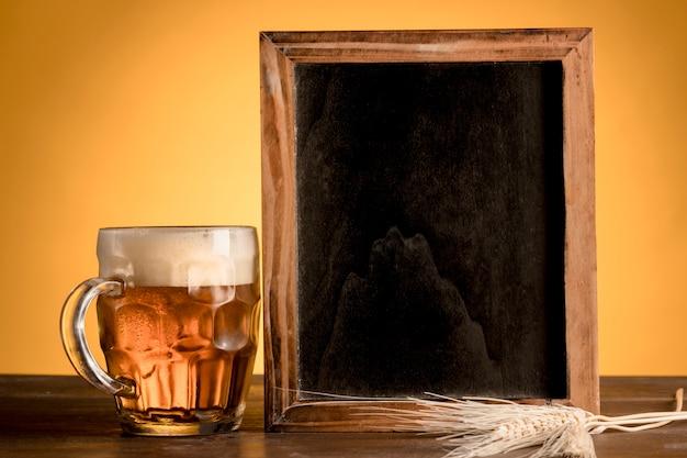 Vaso de cerveza y pizarra en mesa de madera