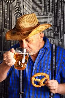 Un vaso de cerveza y un pretzel en manos de un hombre.