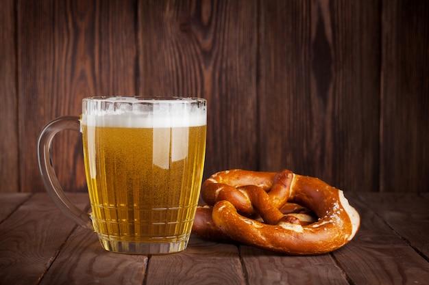 Vaso de cerveza y pretzel en mesa de madera.