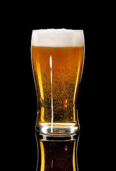 Vaso de cerveza sobre un fondo negro