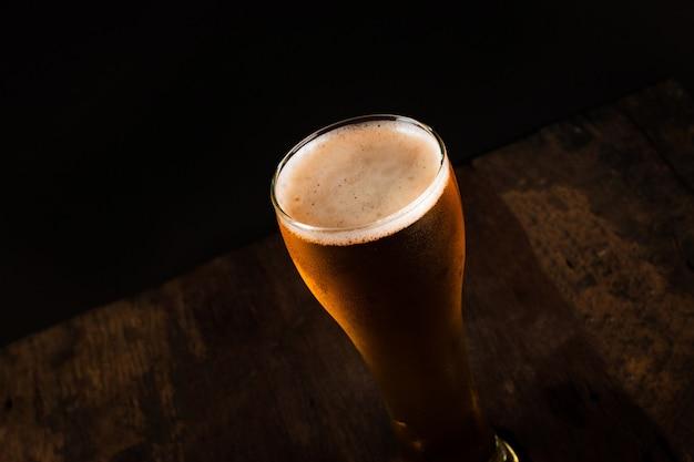 Vaso de cerveza sobre fondo oscuro