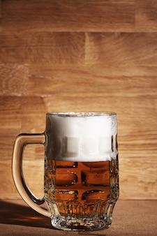 Vaso de cerveza sobre superficie de madera