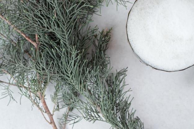 Un vaso de cerveza en la superficie de piedra con rama de pino.