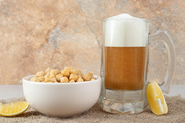 Vaso de cerveza con tazón de guisantes y rodajas de limón en la mesa
