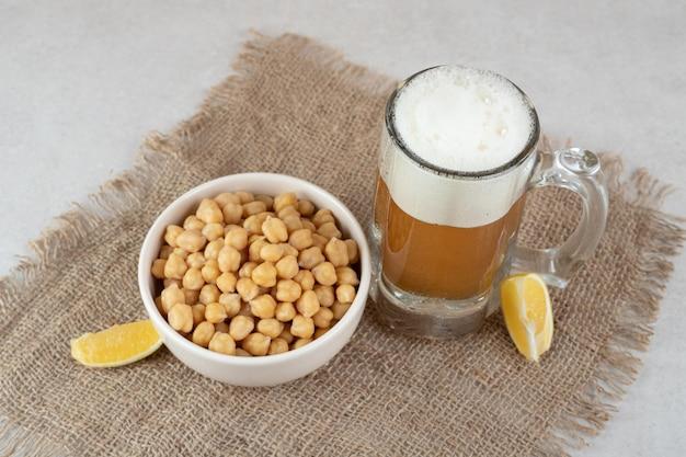 Vaso de cerveza con tazón de guisantes y rodajas de limón sobre arpillera