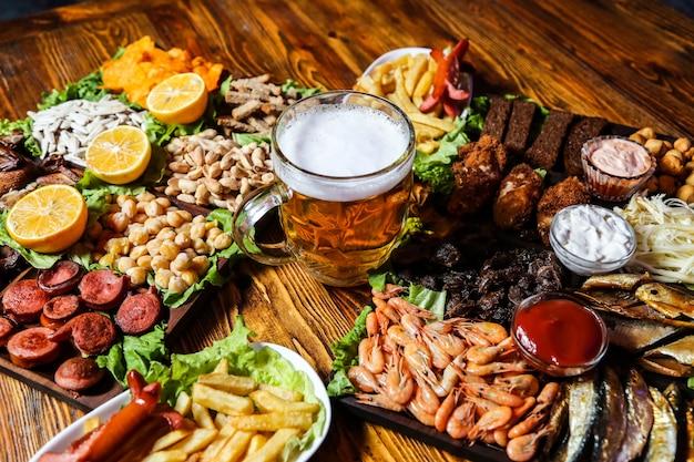Un vaso de cerveza con varios bocadillos en la mesa.