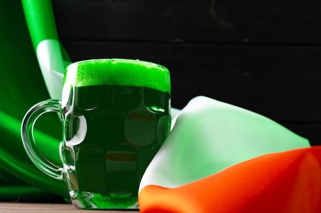 Vaso de cerveza verde contra la bandera de irlanda cerrar