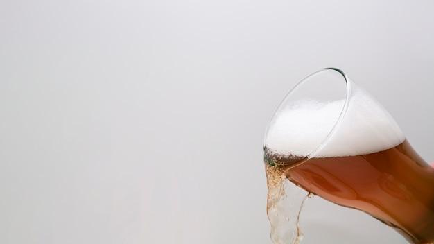 Vaso de cerveza vertiendo con espacio de copia