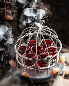 Vaso de chupitos con bebida roja servida en pastel en la sartén ahumada