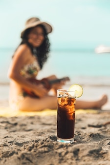 Vaso de coca cola con hielo y mujer en playa de arena