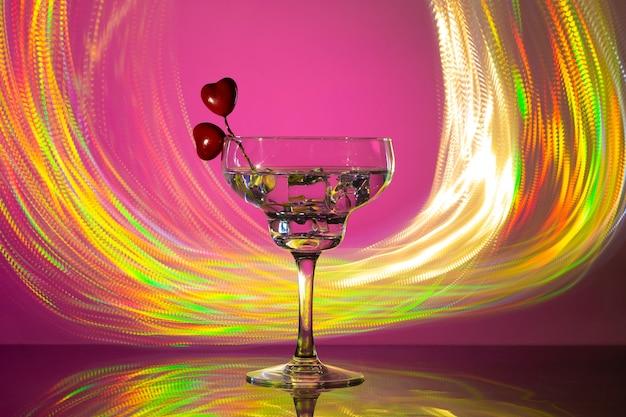 Vaso con un cóctel y dos corazones. día de san valentín y concepto de boda.