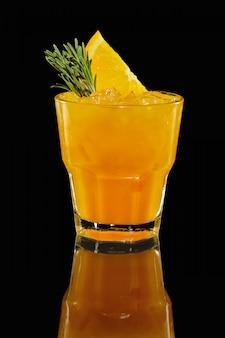 Vaso con cóctel de naranja con reflejo.