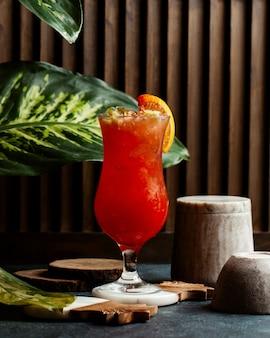 Un vaso de cóctel rojo con hielo y una rodaja de naranja.
