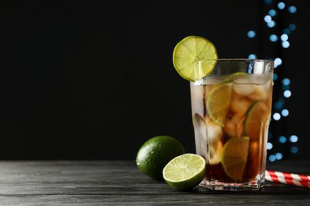 Vaso de cola fría con cítricos y hielo en mesa de madera sobre fondo oscuro