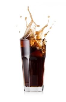 Un vaso de cola fría con un poco de cubitos de hielo.