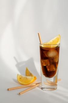 Vaso de cola con hielo, limón y paja sobre un fondo blanco.