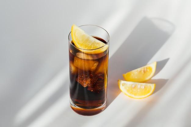 Vaso de cola con hielo y limón sobre fondo blanco.