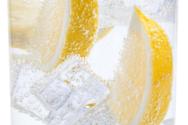 En un vaso con cubos de hielo derretido rebanadas de un jugoso limón amarillo.