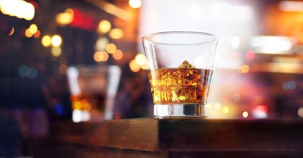 Vaso de bebida de whisky con cubito de hielo en el fondo de la barra de madera de la tabla