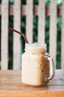 Vaso de café helado en la mesa de madera con estilo de filtro vintage