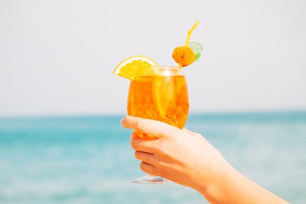 Vaso decorado de increíble bebida de naranja en la mano.