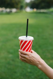 Vaso desechable de papel con una franja roja y blanca de paja para bebidas en manos de una mujer sobre un fondo de hierba verde