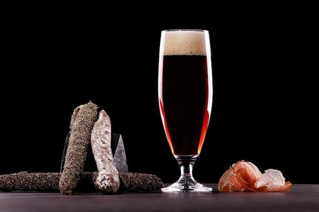 Un vaso de espuma de cerveza oscura, jamón de parma, variedades caras de salchichas. sobre fondo negro. lugar para logo.