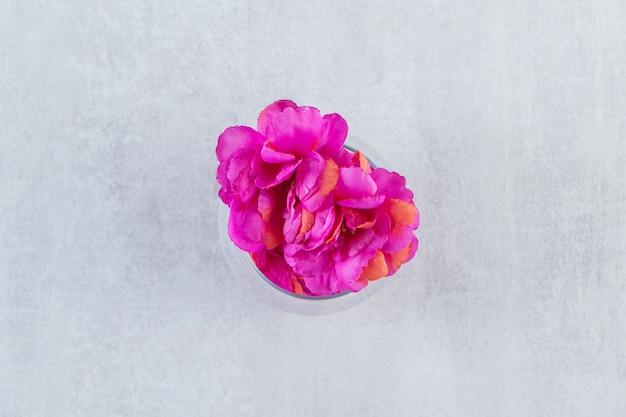 Un vaso de flor morada fresca, sobre la mesa blanca.