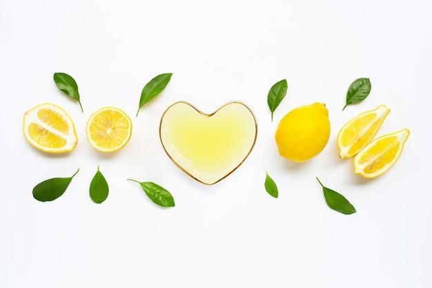 Vaso en forma de corazón de jugo de limón recién exprimido con limón fresco en blanco