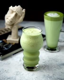 Un vaso con forma única con té verde a juego