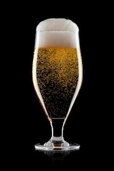 Vaso frío de cerveza artesanal lager ale con espuma y burbujas sobre fondo negro
