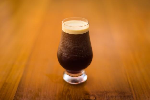Un vaso frío de cerveza oscura sobre una superficie de madera.