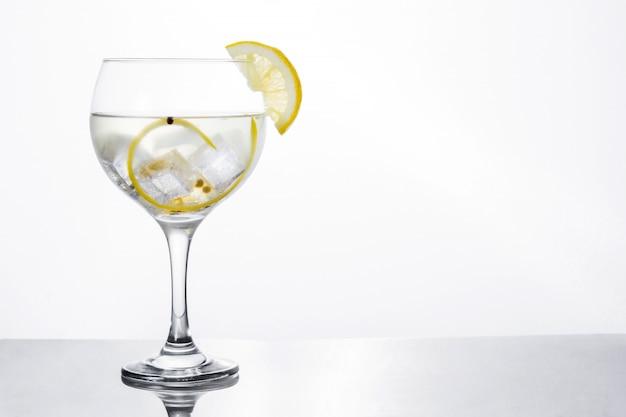 Vaso de gin tonic con limón aislado en blanco