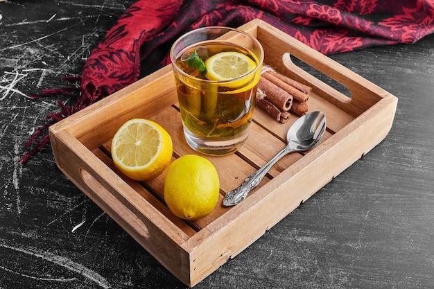Un vaso de glintwine con limones en una bandeja de madera.
