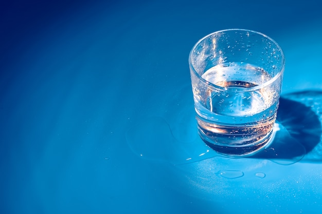 Un vaso con gotas de agua sobre un fondo azul oscuro de cerca