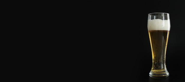 Vaso helado de cerveza dorada fría con burbujas sobre fondo negro. espacio libre para texto, espacio de copia, banner. beber alcohol en fiestas, días festivos, oktoberfest o el día de san patricio.