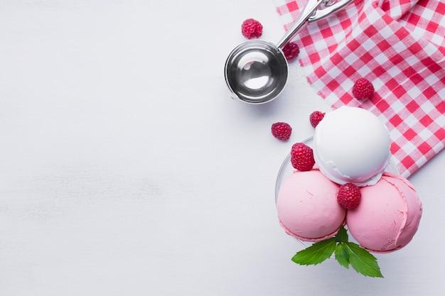 Vaso de helado de frambuesas en mesa blanca