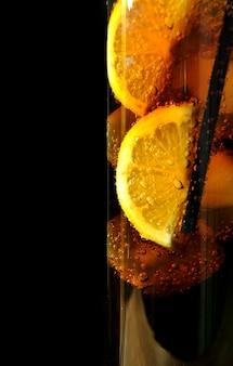 Vaso con hielo de coca cola y limones.