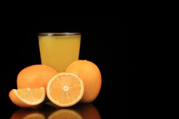 Un vaso de hielo de naranja y fruta de naranja con un fondo negro