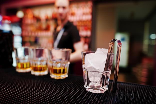Vaso con hielo y pinzas con tres vasos de whisky de fondo barman